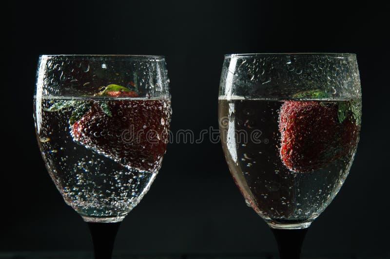 Feche acima, macro Dois cálices de vidro enchidos com chiar o vinho Morango vermelha que flutua em uma bebida alcoólica com bolha imagens de stock