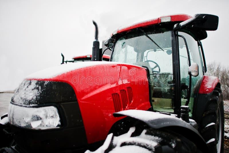 Feche acima na frente do trator vermelho novo no tempo nevado fotos de stock