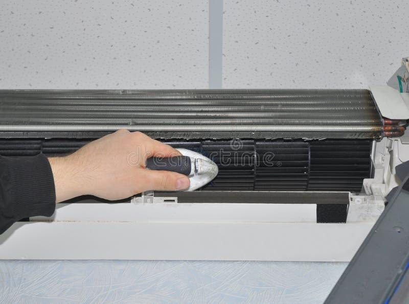 Feche acima na limpeza do condicionador de ar com escova imagem de stock