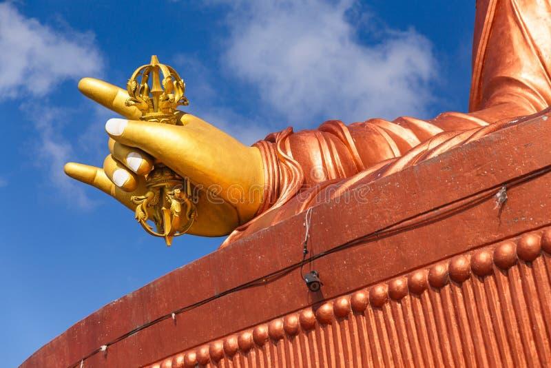 Feche acima na mão dourada direita com macis da estátua de Guru Rinpoche, santo padroeiro de Sikkim em Guru Rinpoche Temple em Na foto de stock