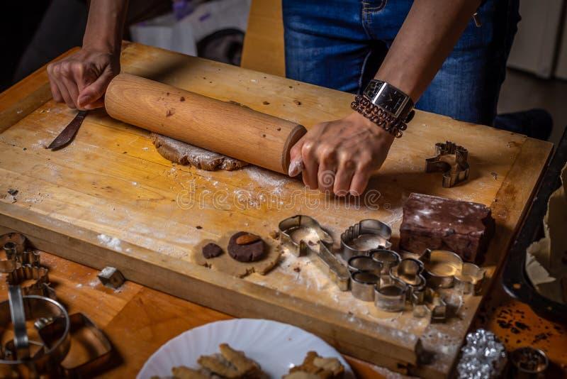 Feche acima na massa de rolamento do pão-de-espécie com formulários, cortadores e ingredientes ao redor fotografia de stock royalty free