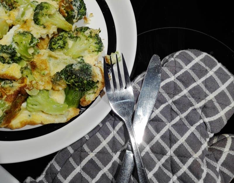 Feche acima na metade de uma placa com omeleta e cutelaria dos brócolis no lado fotos de stock royalty free
