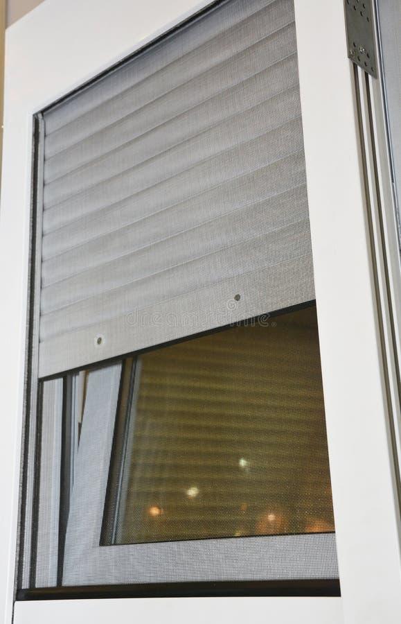 Feche acima na proteção das janelas da casa dos obturadores de rolamento com a tela da rede de mosquito fotos de stock