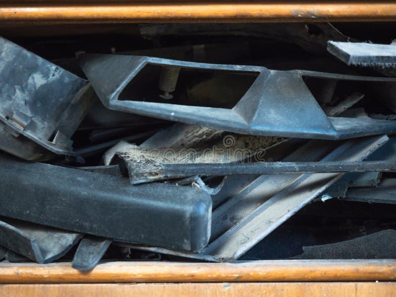 Feche acima nas peças empoeiradas do veículo motorizado que colocam na prateleira marrom da caixa de madeira Fundo diferente das  imagens de stock royalty free