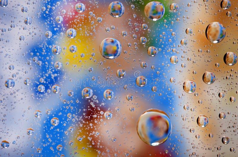 Feche acima no fundo das gotas da água no surfac azul, amarelo, marrom fotos de stock royalty free