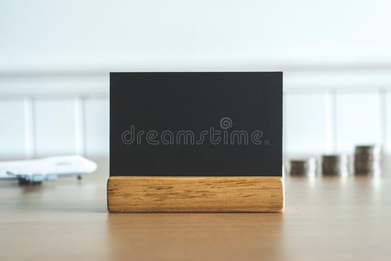Feche acima no quadro-negro com moedas dinheiro e avião no fundo Espaço vazio ou vazio para a mensagem imagens de stock