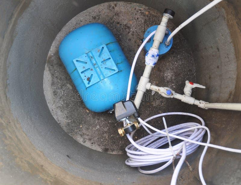 Feche acima no sistema de fonte da água Molhe a perfuração, o acumulador hidráulico, a bomba de água e o outro equipamento fotos de stock royalty free