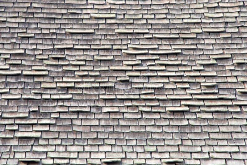 Feche acima no telhado de madeira da telha no reparo pobre, caindo distante foto de stock