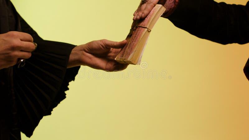 Feche acima para a mão oriental da mulher que dá uma pilha de dinheiro ao vendedor e que obtém relógio redondo, de prata, isolado fotografia de stock royalty free