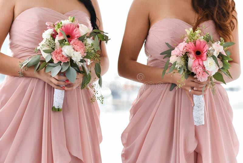 Feche as damas de noiva segurando buquê de flores imagens de stock royalty free