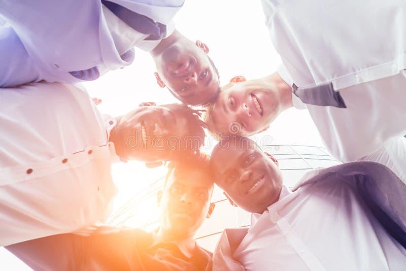 Feche as mãos de um grupo de multinacionais empresário e empresário num aperto de mão de uma reunião de negócios imagem de stock