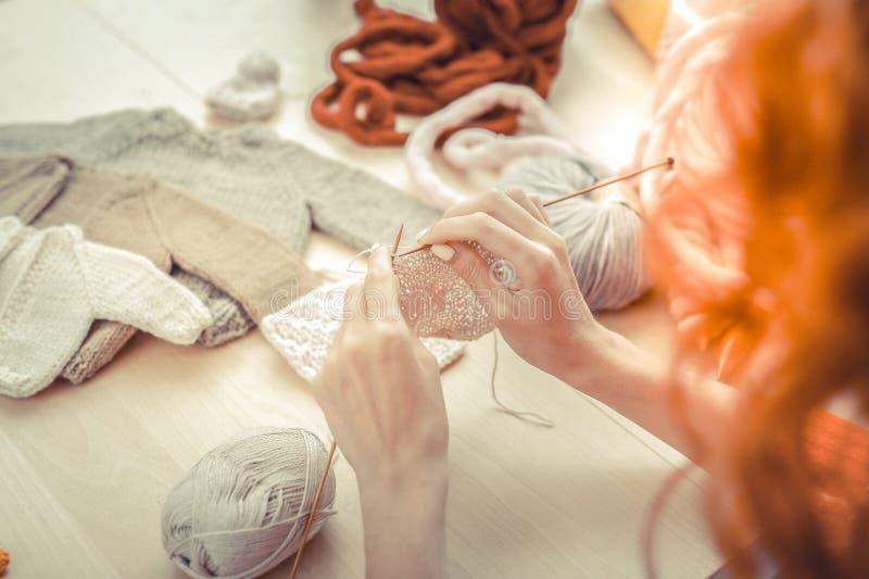 Feche as mãos femininas que tricotam roupas imagem de stock