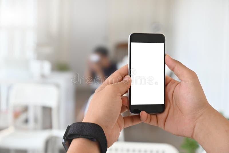 Feche as mãos usando o telefone celular de zombaria foto de stock