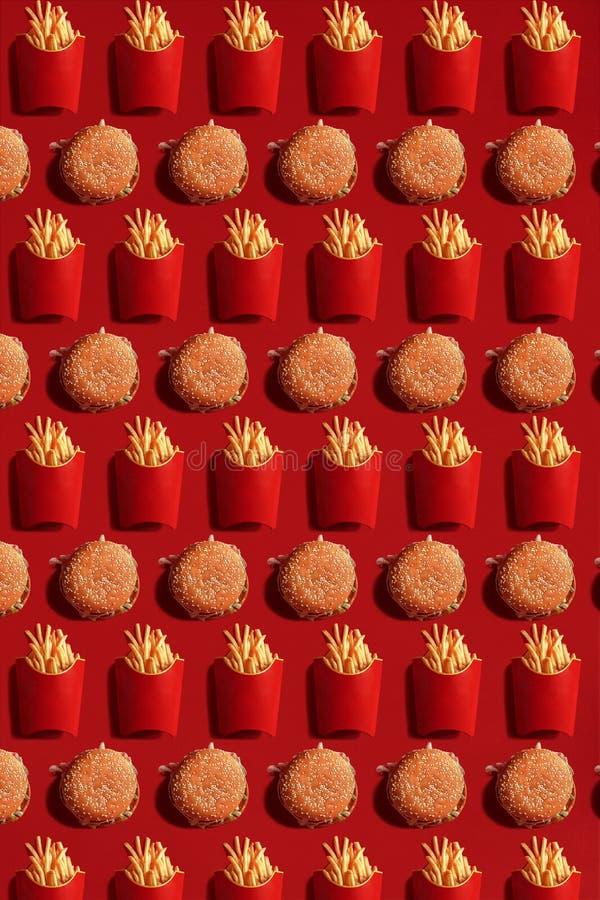 Feche até batatas fritas e hamburgueres, comida lixo alta da caloria, fundo fotografia de stock royalty free