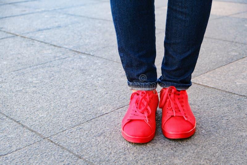 Feche con Los pies de la muchacha en zapatos Zapatillas de deporte rojas y vaqueros Esperar una fecha imágenes de archivo libres de regalías