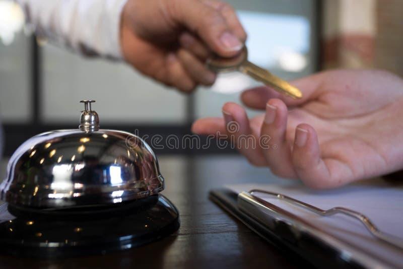 Feche do convidado da mão pega a chave de sala na mesa de registro do hotel Conceito do hotel fotos de stock royalty free