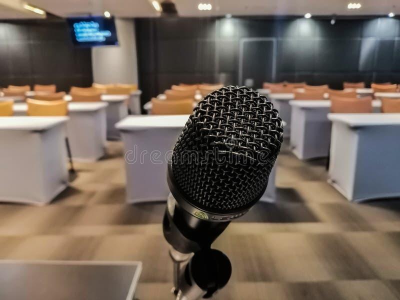 Feche do microfone preto é ficado situado acima na frente da sala de reunião imagem de stock