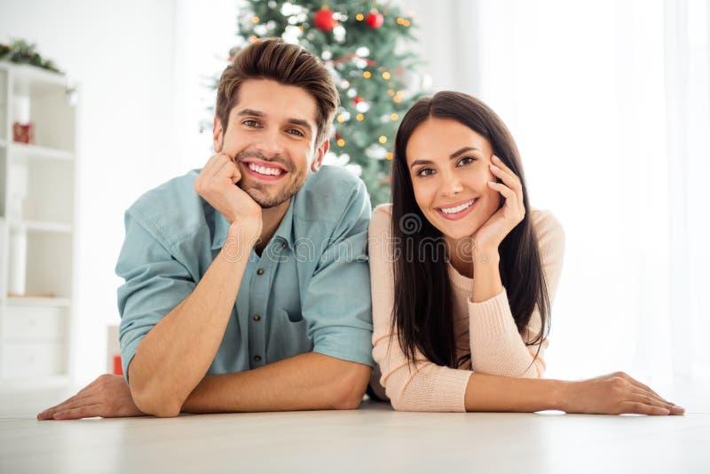 Feche a foto de dois casais deitados no chão aproveitem as férias de Natal em casa em casa foto de stock royalty free