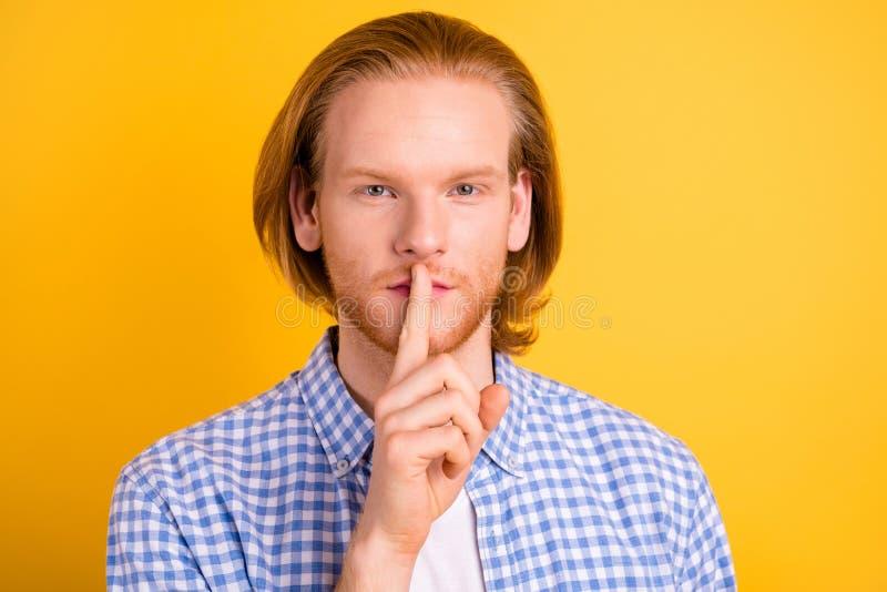 Feche a foto de um homem confiante e sério mostrando para parar de falar tocando seus lábios com o dedo indicador isolado fotos de stock royalty free