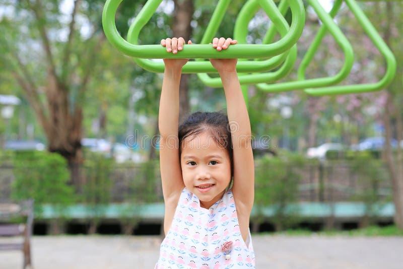 Feche a garotinha brincando no anel de ginástica no playground ao ar livre foto de stock