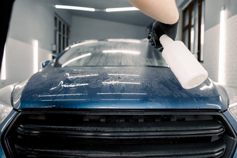 Feche a mão do lavador de carros masculinos em luvas de borracha pretas, limpando a capota azul do carro com uma garrafa de spray imagens de stock