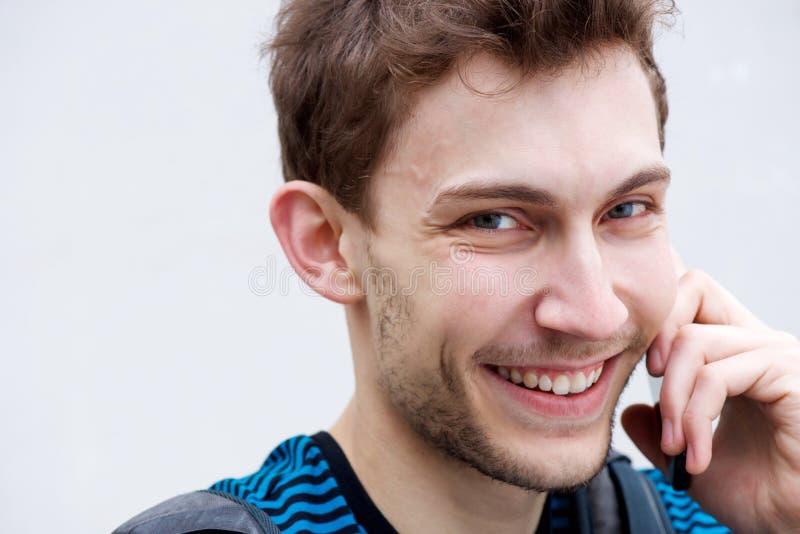 Feche o jovem feliz falando com o celular por fundo branco fotografia de stock royalty free