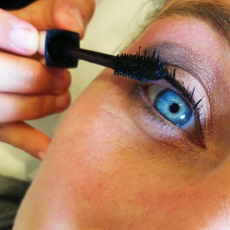 Feche um olho azul, componha rímel num centro de beleza imagens de stock royalty free