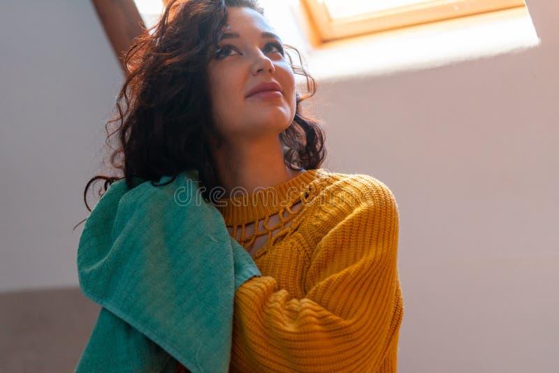 Feche uma morena atraente em um suéter amarelo secando cabelo crespo com toalha azul Método curly de cuidado capilar fotografia de stock