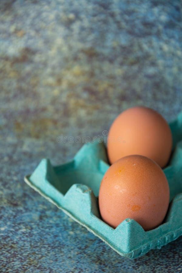 Fecho de dois ovos castanhos em caixa de papelão verde, em fundo desgastado e azulado, em vertica imagens de stock