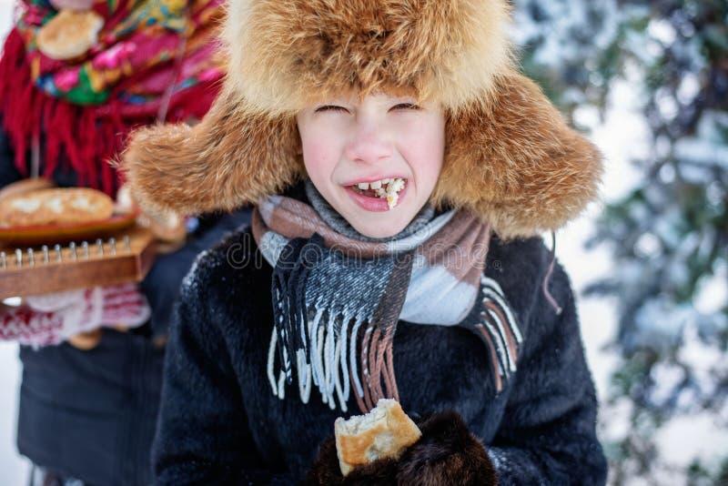 Fecho de um menino no cachecol, chapéu de peles, casaco e luvas, segurando em sua boca um pedaço de tarte mordida fotografia de stock royalty free