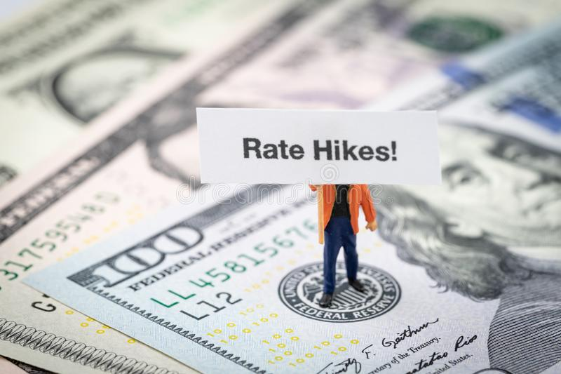 FED consider interest rate hike, world economics and inflation c. Ontrol, miniature man holding Rate Hikes sign standing on US Federal Reserve emblem on dollars royalty free stock photography