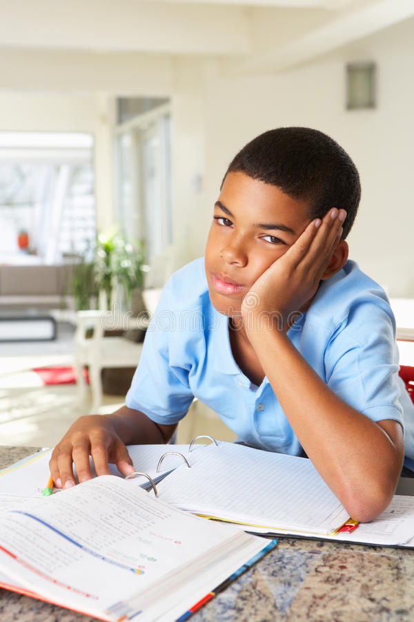 Fed Up Boy Doing Homework In Kitchen stock photo