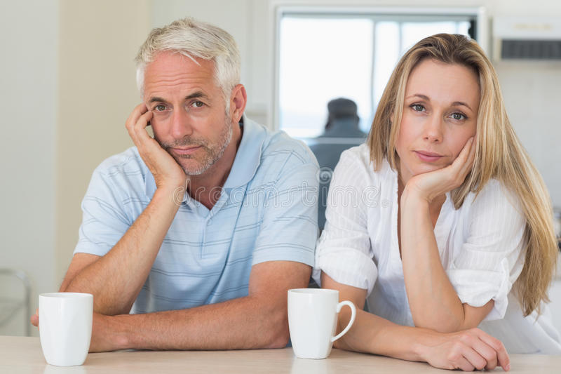 Fed up couple sitting at the counter. At home in the kitchen royalty free stock image