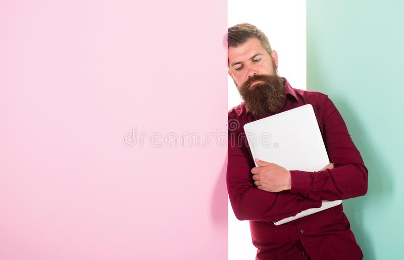 Fed up with creativity. Man bearded hipster worker with laptop lean on wall. Guy web developer programmer or designer stock image