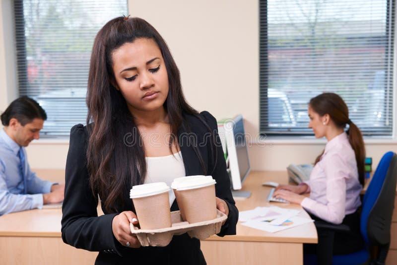 Fed Up Female Intern Fetching kaffe i regeringsställning arkivfoto