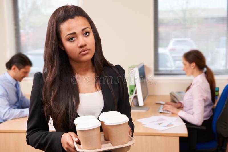 Fed Up Female Intern Fetching kaffe i regeringsställning arkivbilder