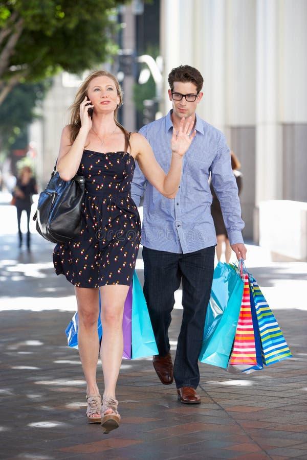 Fed Up Man Carrying Partners-Einkaufstaschen auf Stadt-Straße stockfoto