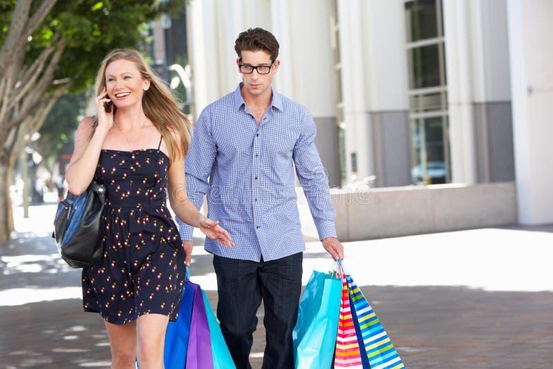 Fed Up Man Carrying Partners shoppingpåsar på stadsgatan fotografering för bildbyråer