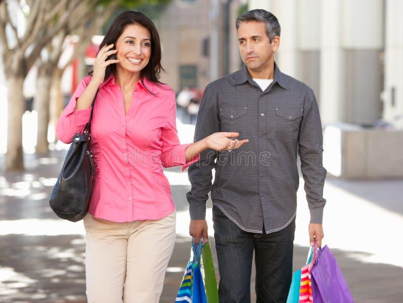 Fed Up Man Carrying Partners shoppingpåsar på stadsgatan arkivfoton