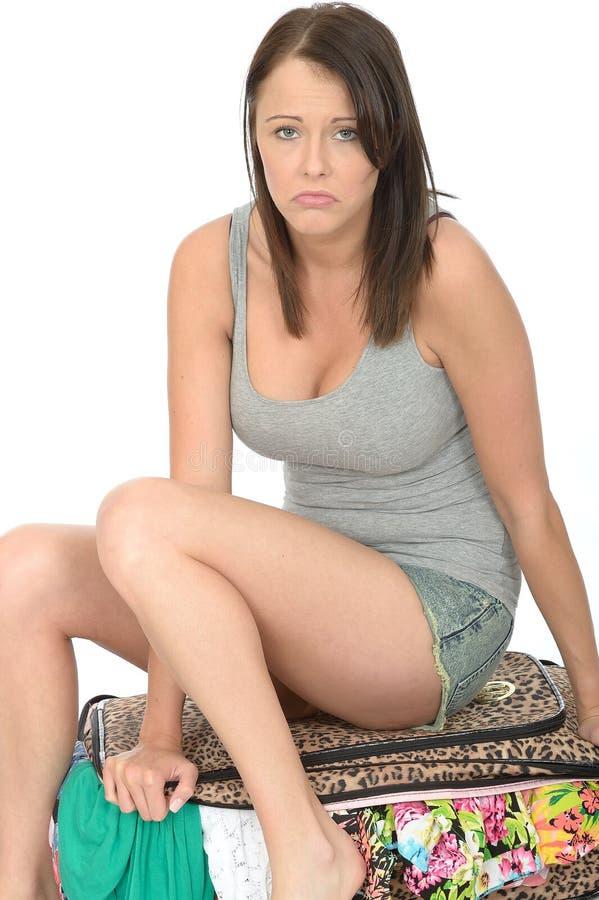 Fed Up Stressed Young Woman triste que senta-se em uma mala de viagem completa de transbordamento imagem de stock