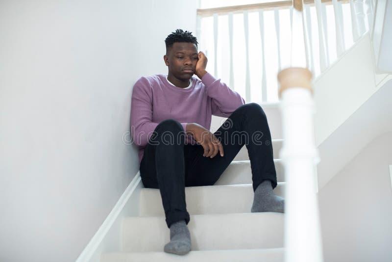 Fed Up Teenage Boy Sitting sur des escaliers à la maison images stock