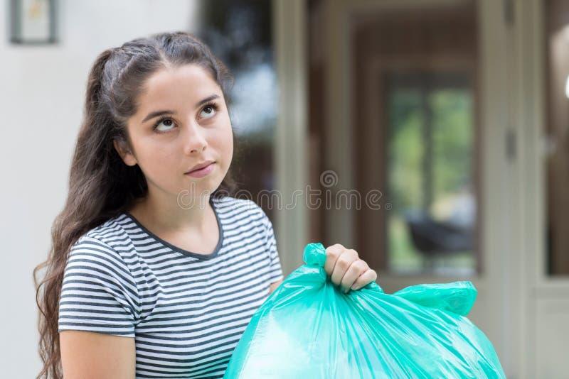 Fed Up Teenage Girl Taking hacia fuera Rubbish en casa fotografía de archivo
