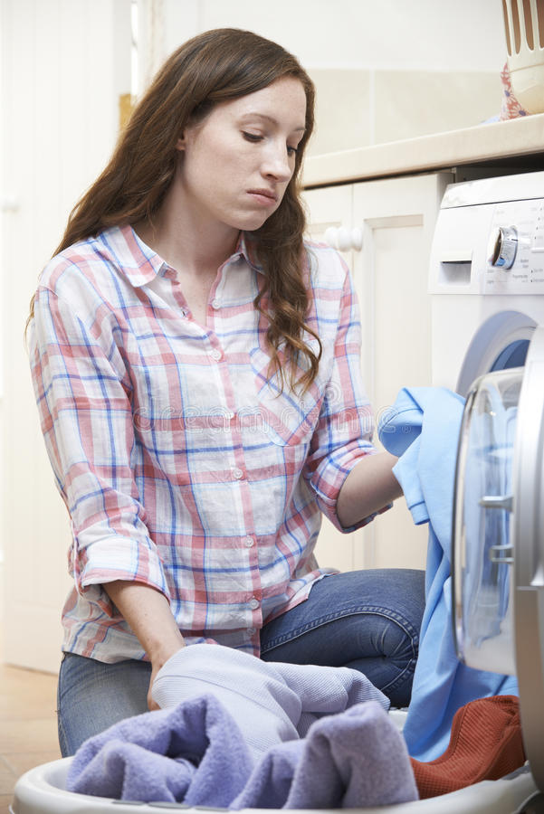 Fed Up Woman Doing Laundry zu Hause stockbild