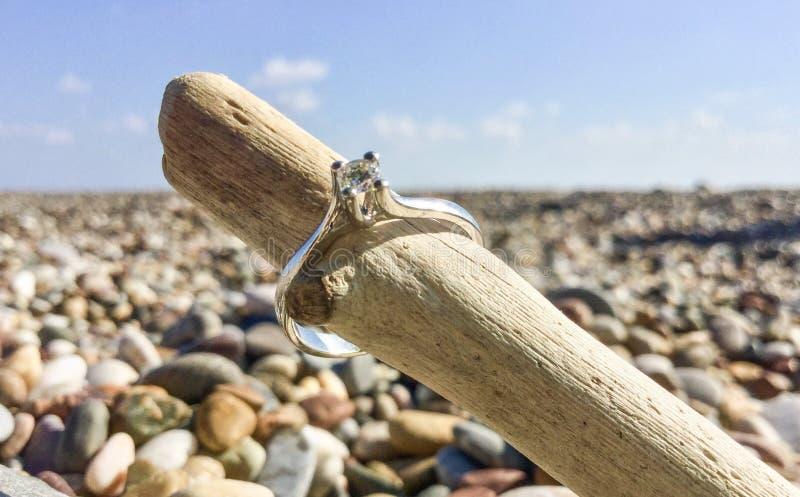 Fede nuziale del diamante sulla spiaggia immagini stock