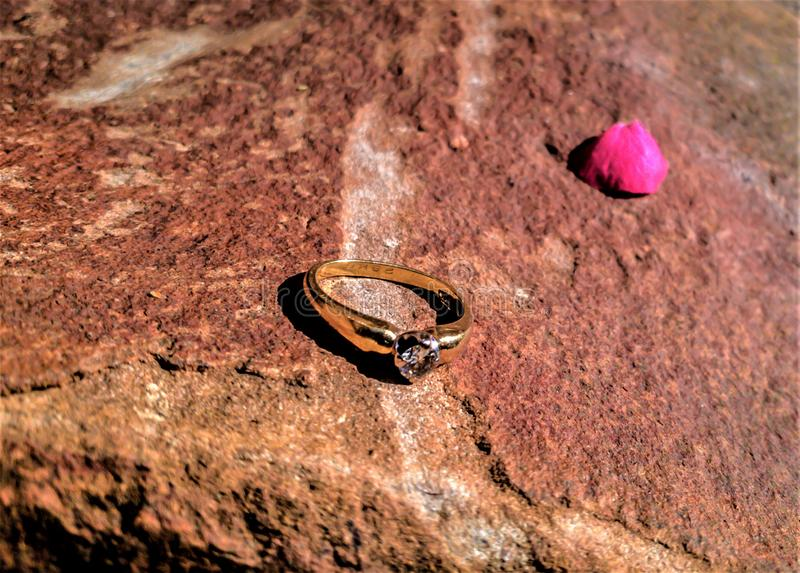 Fede nuziale dell'oro su una superficie della roccia immagine stock libera da diritti