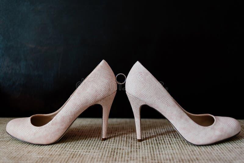 Fede nuziale fra le scarpe del ` s della sposa su un fondo scuro fotografia stock libera da diritti