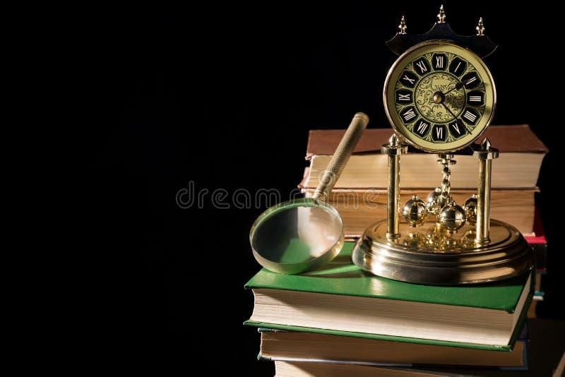 Feder auf dunklem Hintergrund gegen alte Bücher Lupe nahe Weinleseuhr auf alten Büchern gegen schwarzen Hintergrund stockbild
