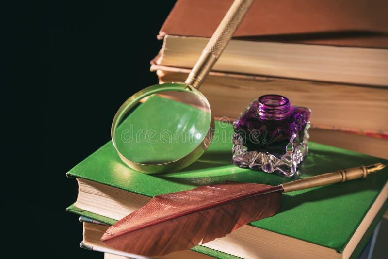 Feder auf dunklem Hintergrund gegen alte Bücher Schreibtischgarnitur mit Feder nahe Lupe auf alten Büchern gegen schwarzen Hinter stockfoto
