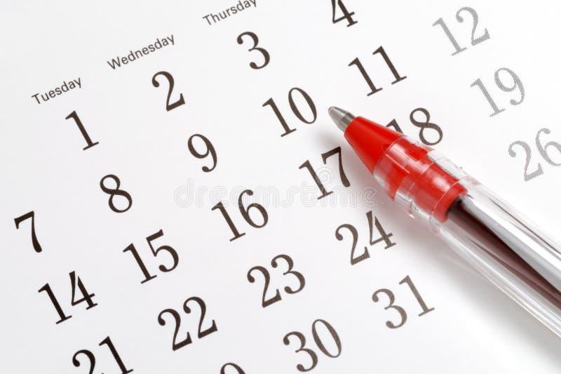 Feder auf Kalender stockbilder