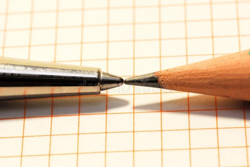 Feder und Bleistift gegenüber von einander stockfotos
